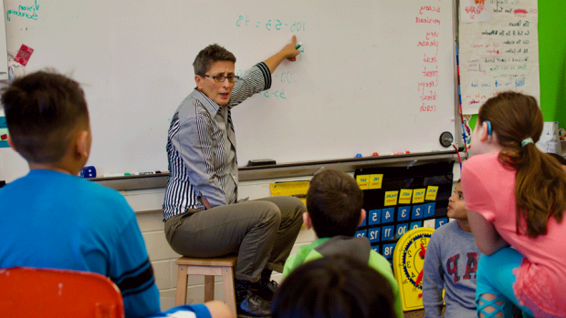 Photo of a teacher sitting on a stool next to a white board in front of a group of students
